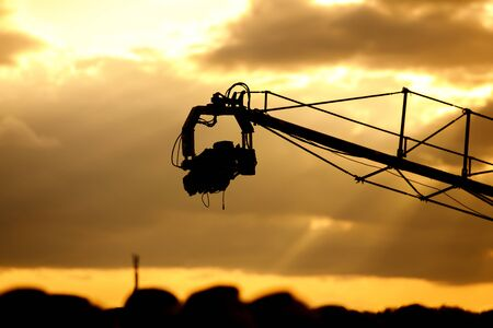 TV camera on a crane on outdoor shooting, sunset