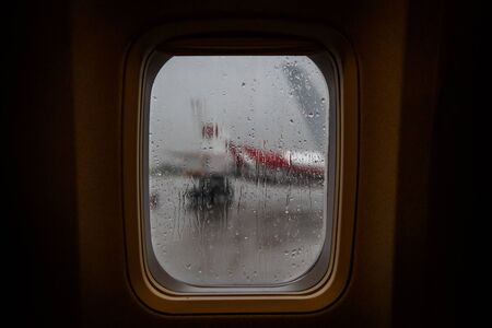 Raindrops on the window glass of an airplane.