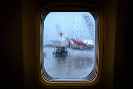 Raindrops on the porthole of an airplane.