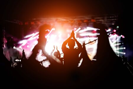Silhouette of a girl with raised at a concert