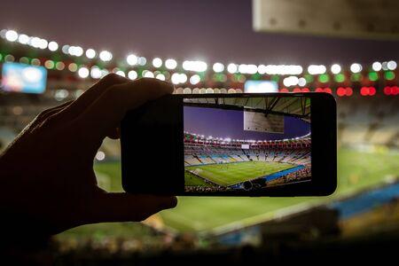 Using a smartphone on soccer stadium