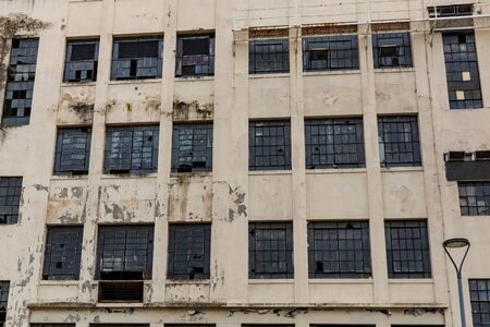 The facade of an abandoned building. Broken windows and peeling paint
