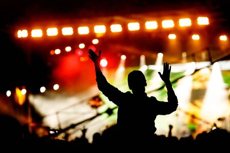 Silhouette of man with raised hands on concert. Crowd on music show