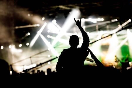 Silhouette of man with raised hands on concert. Crowd on music show Stock Photo