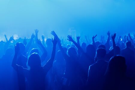 Silhouette of people with raised hands on concer. Crowd on music show