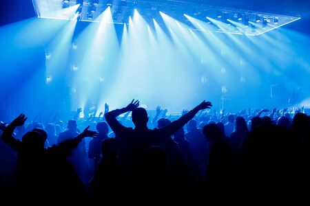 Silhouette of people with raised hands on concer. Crowd on music show Stock Photo