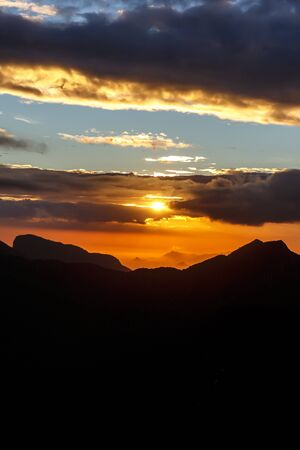 Sunset. The sun above the line of mountains
