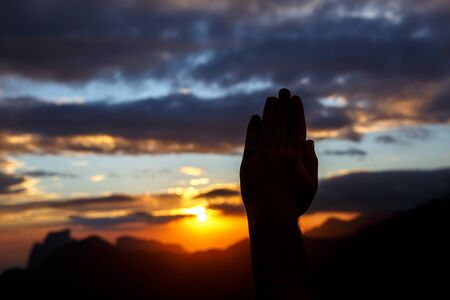 Praying hands on sunset background. Black silhouette