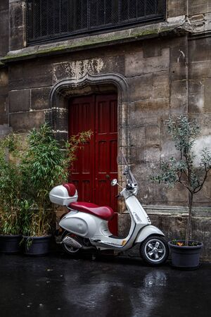 The scooter parked near red door