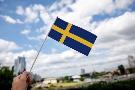 Swedish flag on city background