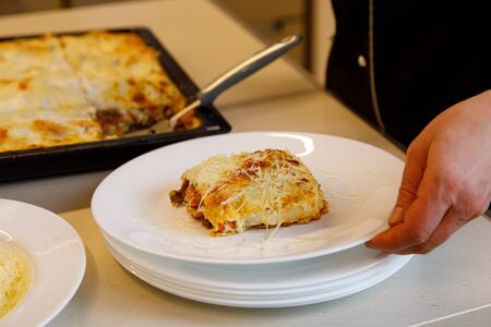 Cook puts a piece of fresh lasagna on a white plate