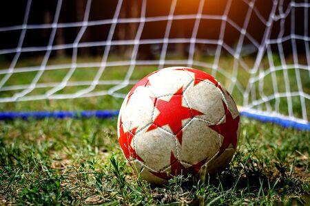 Soccer ball on green grass with a goal net