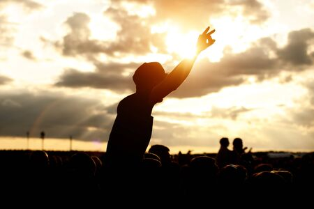 A man in a cap and raised arms takes pleasure at an outdoor music festival. Black silhouette on sunset