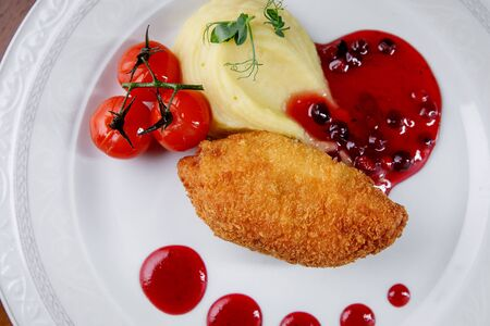 Kiev chicken cutlet with mashed potatoes and berry sauce on a white plate