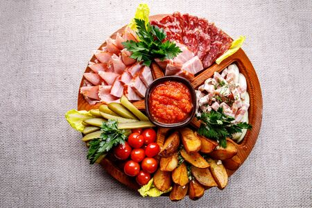 Round wooden tray with different snacks. Ham, vegetables, pickles, cherry tomatoes and sauce in the center