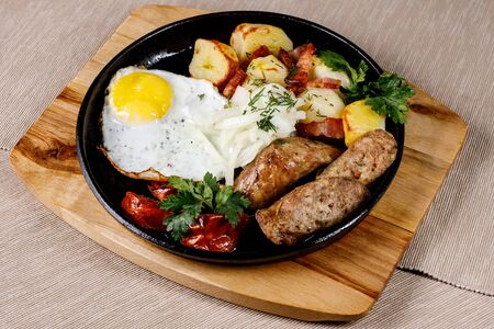 Pan with fried potato, meat, sausages, eggs, and vegetables Imagens