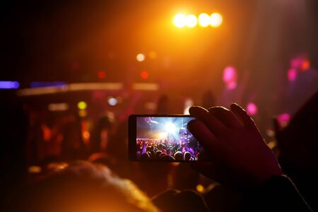 Mobile phone in hands at a music show. Using a smartphone concept