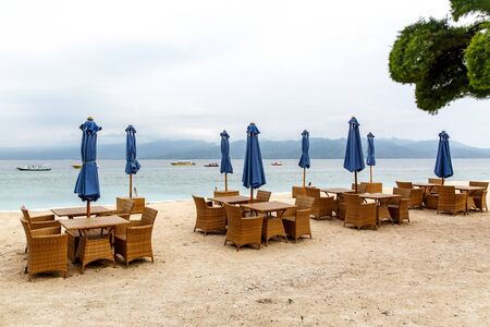 Empty tables of the beach cafe. Folded umbrellas, lack of tourists
