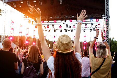 Girl with raised hands on outdoor music festival