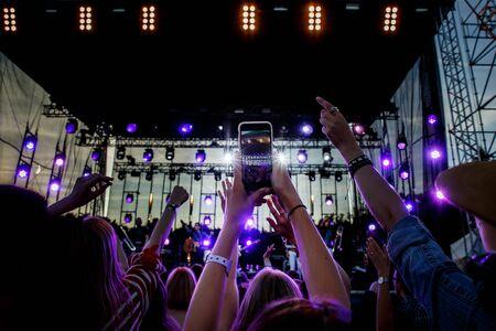 人们用举的手在夏天音乐节。音乐会乐趣