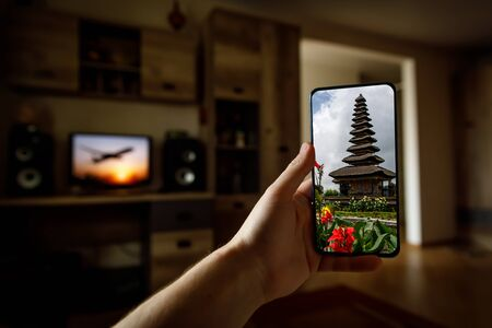 Online travel to Bali island via mobile phone from home Stock Photo