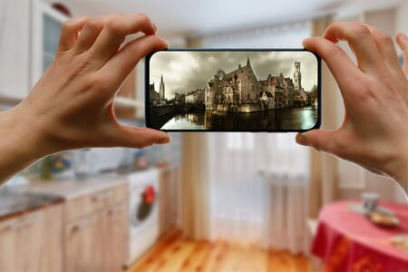 Looking at medieval city Brugge on a mobile phone screen from home. Online tourism concept