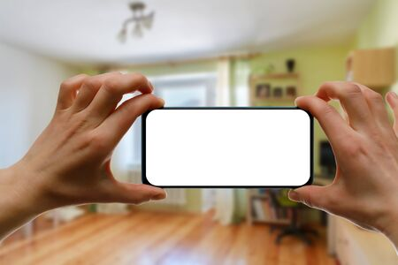 The concept of using a mobile phone at home. Blank white screen for your image.