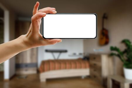 Mockup of using a smartphone in the home interior. Blank white screen for your idea