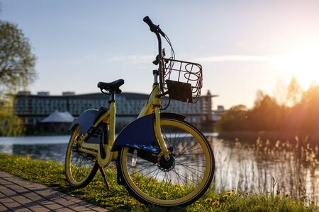 Yellow rental bike in the city. Sunset near the pond