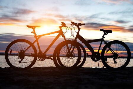 Black silhouette of a bicycle at sunset on the beach near the lake