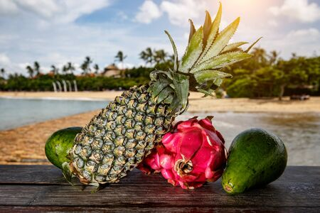 Dragon fruit, avocado and pineapple on exotic beach background. Fruits mix