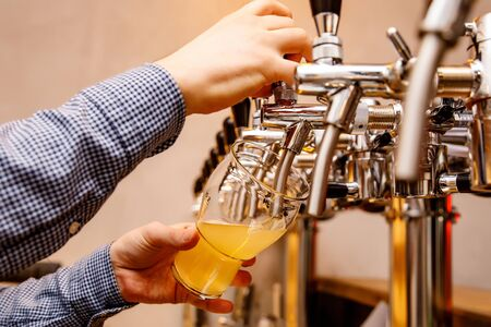 The bartender pours fresh light beer from the tap in the pub