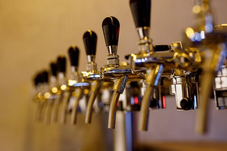 A row of beer taps in a bar.