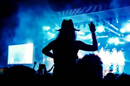 Silhouette of a girl with raised hands at a mass event. Party in a nightclub.