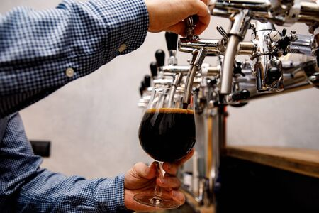 The bartender pours fresh black beer from tap in the pub
