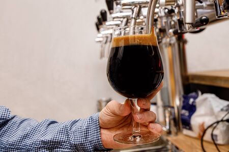 The bartender pours fresh dark beer from tap in the pub