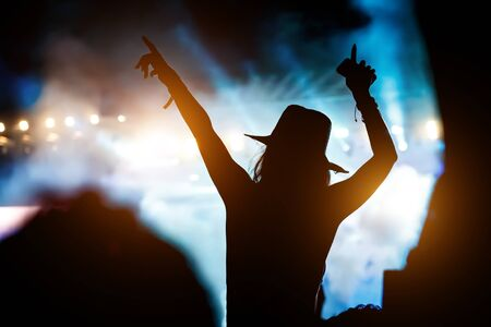 Silhouette of girl with raised hands on music concert. Stock fotó