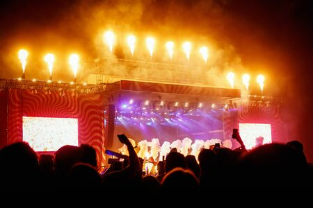 Big concert stage with fire production at outdoor music festival