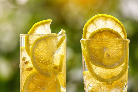 Glass of lemon water on the sunny garden background. Close-up view