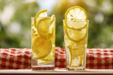 Glasses of lemonade with lemon on the sunny garden background