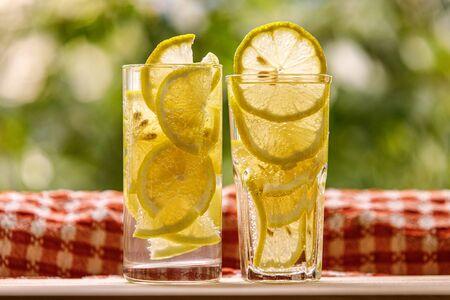 Glasses of lemon water on the sunny garden background
