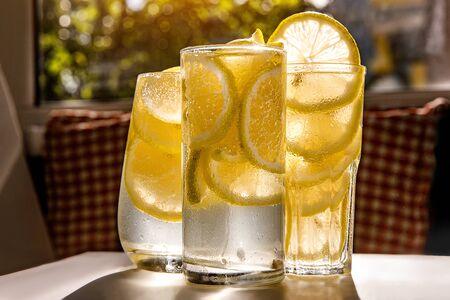 Glasses of lemonade with lemon on the sunny room background
