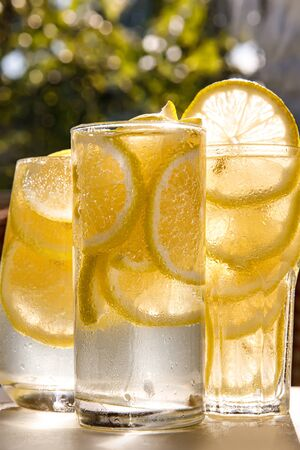 Three glasses of lemon water on the sunny garden background. Close-up view