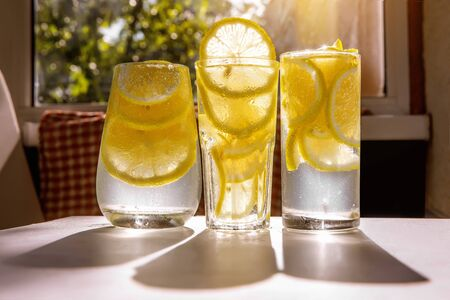 Three glasses of lemon water on the sunny room background