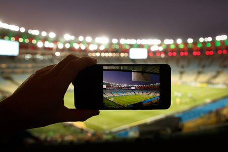 Smartphone photographing football game on the stadium. Stock Photo