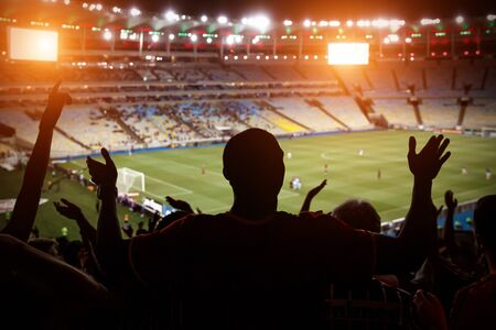 Silhouette of fan celebrating a goal on football match. Support team on soccer game.