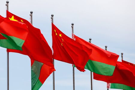Belarusian and Chinese flags fluttering in the wind Stock fotó