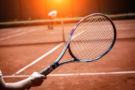 The player holding a tennis racket. Clay tennis court