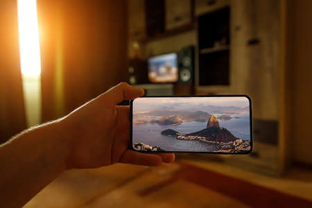 Concept of travel on a smartphone. Stay at home tourism. Online travel to Rio-De-Janeiro. Sugarloaf on a screen.