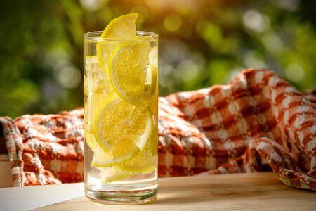 Glass of lemonade with lemon on the sunny garden background